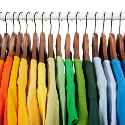 8189015 - rainbow colors. choice of casual clothes on wooden hangers, isolated on white.